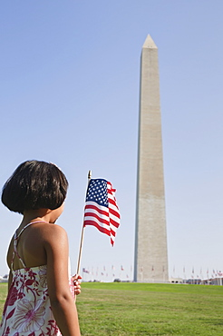 USA, Washington DC, girl (10-11) with US flag in front of Washington Monument
