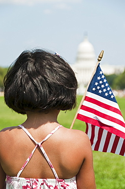USA, Washington DC, girl (10-11) with US flag in front of Capitol Building