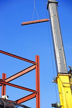 Crane holding steel girder