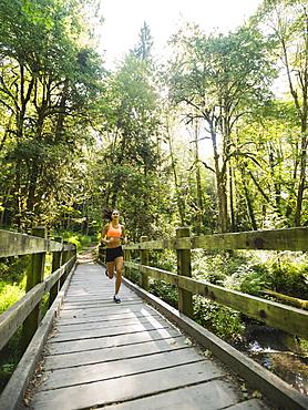 Young woman jogging on footbridge, USA, Oregon, Portland