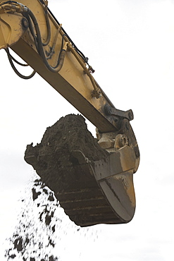 Low angle view of digger scoop full of soil