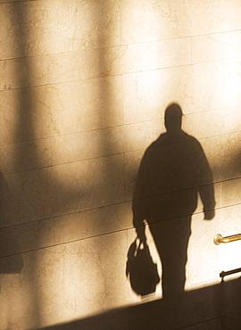 Shadow of male pedestrian on sunlit wall
