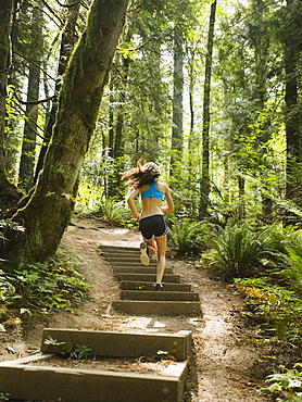 Rear view of young woman jogging in forest, USA, Oregon, Portland