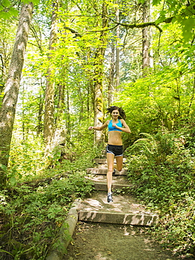 Young woman jogging in forest, USA, Oregon, Portland