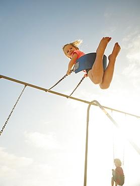 Girl (4-5) and boy (2-3) swinging on beach, San Clemente, California