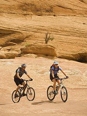 Couple riding mountain bikes in desert