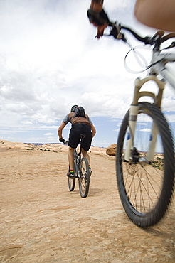 Low angle view of couple riding mountain bikes