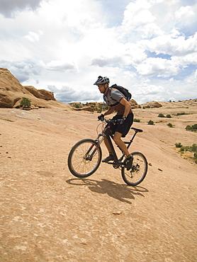 Man riding mountain bike on rock formation