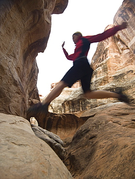 Woman jumping over rock formations