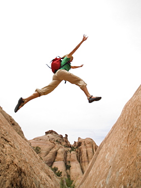 Woman jumping over rock formation