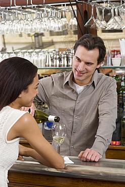 Male bartender pouring wine for female customer