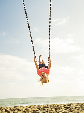 Girl (4-5) swinging on beach, San Clemente, California