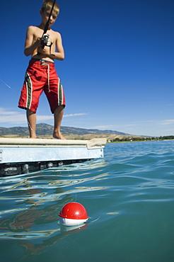 Boy fishing off dock in lake, Utah, United States