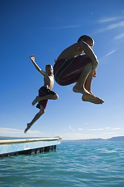 Brothers jumping off dock into lake, Utah, United States