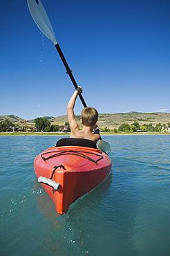 Boy paddling in canoe on lake, Utah, United States