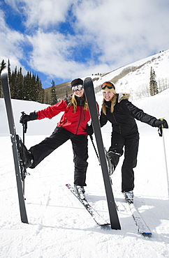 Woman standing on skis with legs up