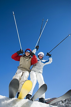 Couple with arms raised on skis