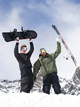 Snowboarders holding snowboards over heads