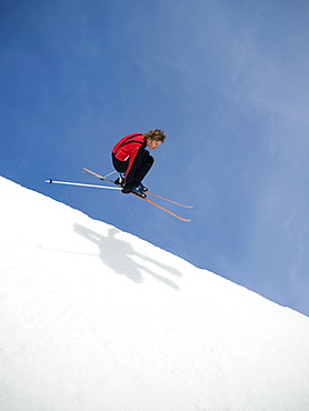 Skier jumping off lip of half-pipe