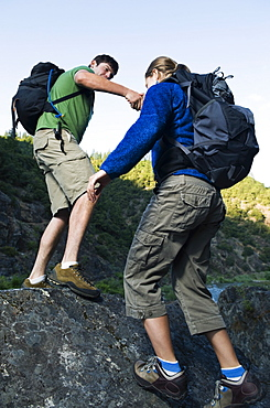 Man helping female hiker up rocky slope