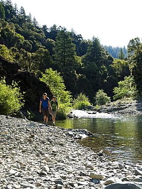 Hikers walking along river