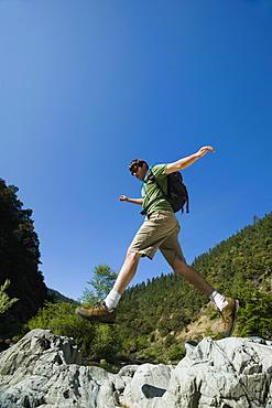 Hiker jumping across rocks