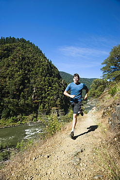 Man running on riverside trail