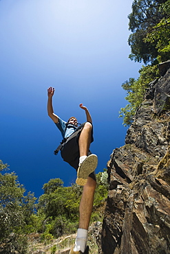 Hiker jumping down rocky trail