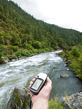 Man holding gps unit by river