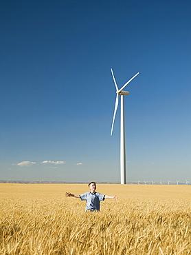 Boy running through field on wind farm