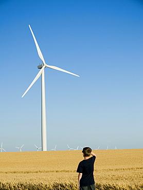 Boy looking at windmill on wind farm