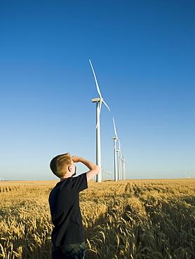 Boy looking up at windmills on wind farm