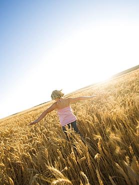 Girl running through tall wheat field