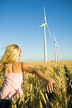 Girl running through tall wheat field on wind farm