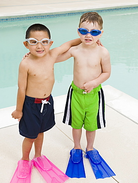 Boys in flippers posing by swimming pool