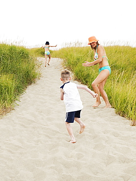 Mother running on beach with daughter and son