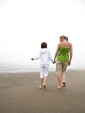 Mother and daughter holding hands and walking on beach