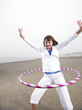 Portrait of girl with hula hoop on beach