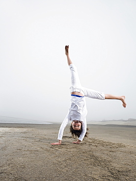 Portrait of girl doing handstand on beach