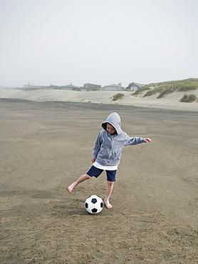 Boy kicking soccer ball on beach