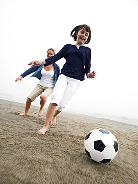 Mother and daughter playing soccer on beach
