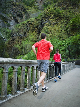Couple running across bridge