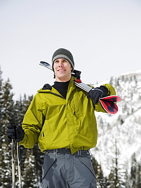 A downhill skier carrying skis