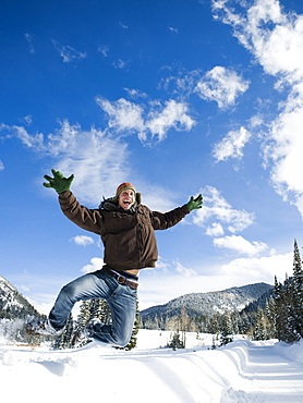 A man outdoors in snowy surroundings jumping