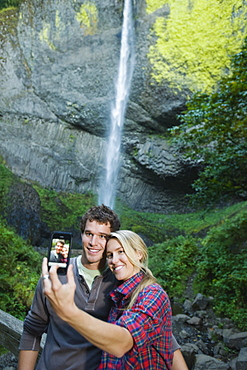 Couple taking picture in front of waterfall