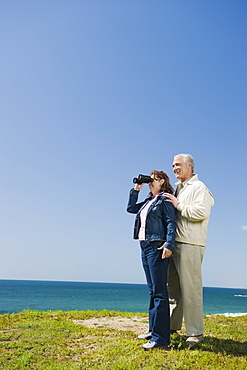 Couple looking at ocean with binoculars