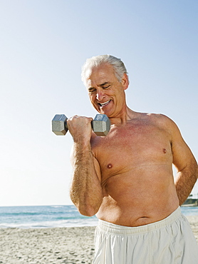 Man exercising with dumbbell on beach