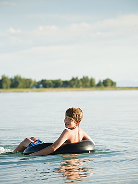 Boy (12-13) floating on rubber ring on lake