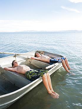 Boys (10-11,12-13) resting on boat