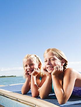 Girls (6-7-7,8-9) resting on raft on lake
